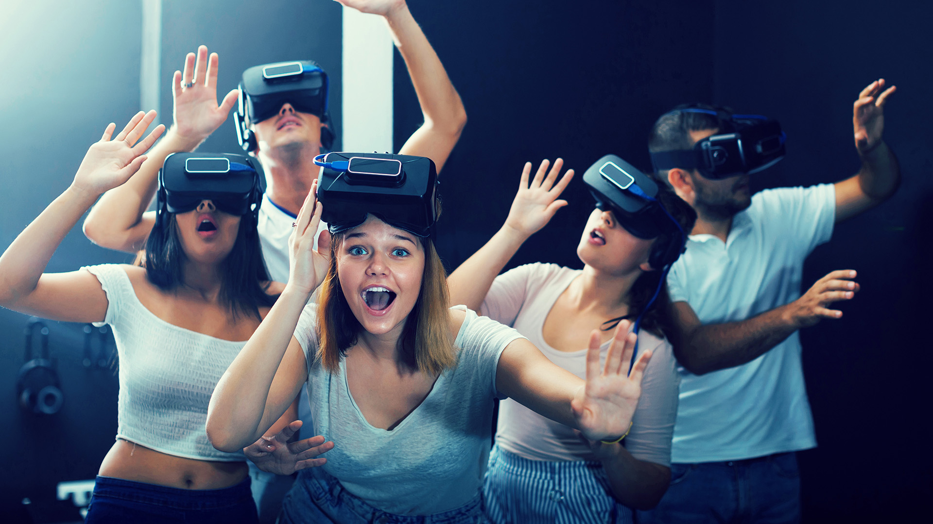 Young american scared girl on virtual reality attraction sitting with another people