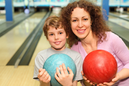 beautiful young mother and son keep red and blue balls in bowling club